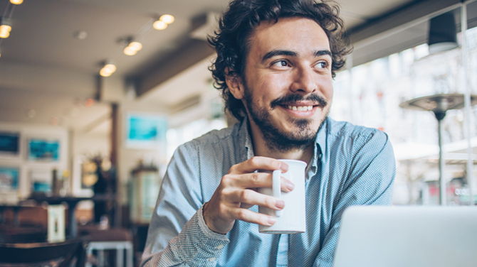 man with coffee at computer